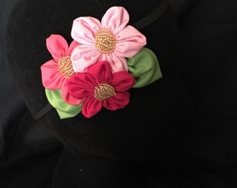 Bright pink floral fascinator with gold beaded accents