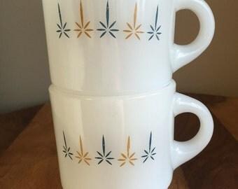 Pair Of Two Fire King Glow Starburst Mugs, Blue & Golden Pattern, Milk Glass Stacking C Handle.