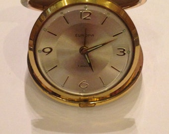 German Europa Travel Alarm Clock in an embossed folding shell, good condition.
