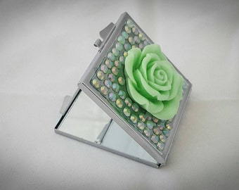 Square compact mirror in green with a large flower