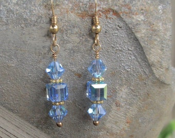 Delicate gold filled earrings with light blue Swarovski bicone and cube crystals on a gold filled ear wire