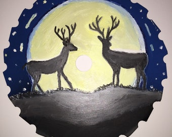 Hand painted saw blade with picture of deer in front of moon.