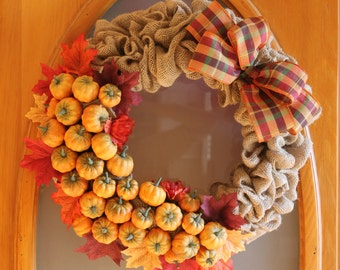 Burlap wreath with decorative fall leaves, pumpkins and bow