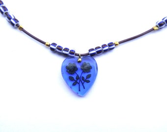 Necklace made of vintage blue glass heart with roses, new beads, metal button beaded on leather cord