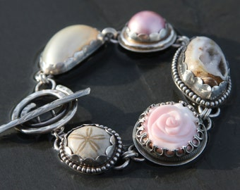 mother of pearl, mabe pearl, fossil shell, carved conch shell, fossil sand dollar and sterling silver metalwork link bracelet