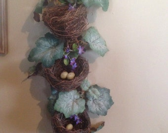 A decorated grapevine and triple birdnest swag wall hanging