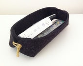 Remote control holder in wool felt with leather or cotton ties.