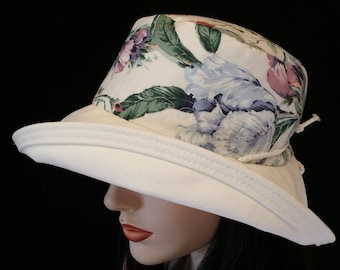 Sunblocker - Large brim sun hat with adjustable fit featuring very cream floral print with muted pastel flowers