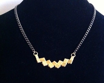 Chevron pendant on gunmetal long chain