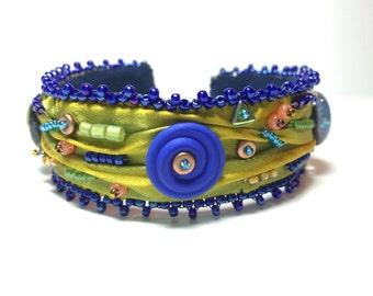 Shibori silk bangle bracelet with dichroic glass and lampwork disc focals