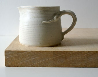 Wheel thrown pouring jug - with little mouse attached glazed in vanilla cream