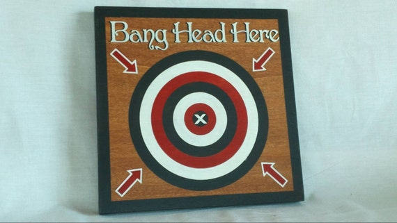 Bang Head Here. Painted wooden sign