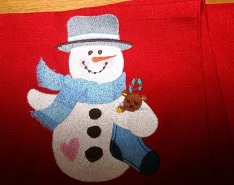 embroidered napkin with snow man holding xmas stocking