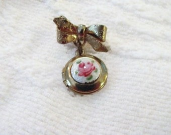 Sweet little Bow with dangling gold plated locket pin.  Rose enamel guilloche.