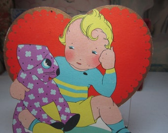 Adorable 1930's die cut gold gilded large Carrington Co. valentine card rosy cheeked boy sits with a colorful purple colored stuffed toy dog