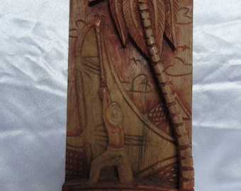 Wooden plaque features a tropical scene with a man and a boat and a palm