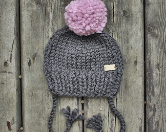 Charcoal grey chunky knit baby hat with light pink pom-pom & ties