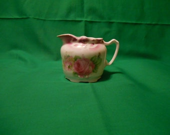One (1), 8 oz, Porcelain Creamer, Marked Germany, in a Floral Pattern.