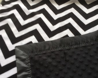 A chevron print in black and white minky blanket  ,it has a black satin binding around it. The chevron is shannon brand minky.
