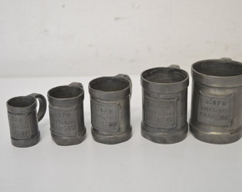 Five pewter small cups for gun powder, 1920s