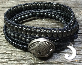 Black four-wrap boho bracelet with silver art deco button and silver charm