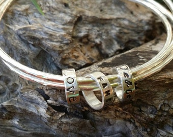 Sterling silver stacking bangles with inspiration message beads. Personalized stacking bangles. Spinning bangles. Made in Australia.