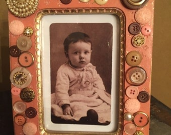 Peachy-pink and gold wood frame adorned with vintage buttons and jewels.  Holds a 4x6 photo.