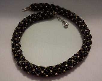 It's a Black Spiral necklace decorated with brown Seed Bead.