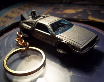 custom made stock keychain,1985 delorean-back to the future time machine-hover-mode,metallic silver w/black mags/stock-mint