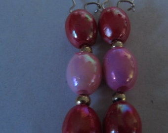 Silver earrings made with pink and red beads.