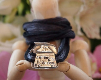 A cute little typewriter hand made in fine silver on a hand dyed grey and black silk wrap bracelet...