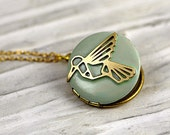 NEW: Small hummingbird locket necklace. Light bluegreen enameled locket with embedded hummingbird. Short golden brass necklace.
