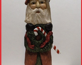 HAND CARVED SANTA Holding Candy Cane & Wreath. Turn Santa over and you will find he put another candy cane in his pocket.