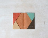 deep orange textured leather card holder with triangle design on inside and mint painted edges / Travel card holder