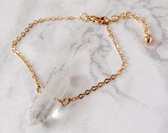 Bracelet in gold with a white acrylic crystal.