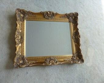 Gold ornate framed beveled mirror.