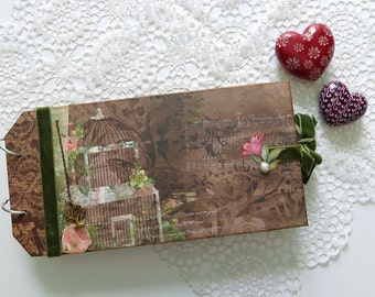 Girly scrapbook photo album journal with brown pink and green patterned paper with dots stripes and flowers.