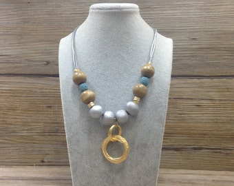 Elegant long leather strings necklace with beads and gold plated elements.
