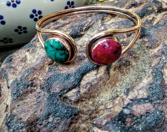 copper bracelet with turquoise and rhyolite stone.