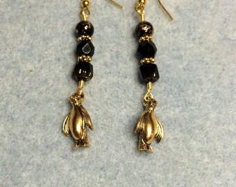 Gold penguin charm earrings adorned with black Czech glass beads.