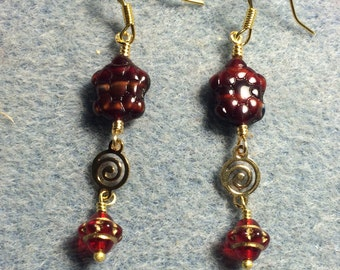 Red marbled Czech glass turtle bead dangle earrings adorned with gold swirly connectors and red Saturn beads.