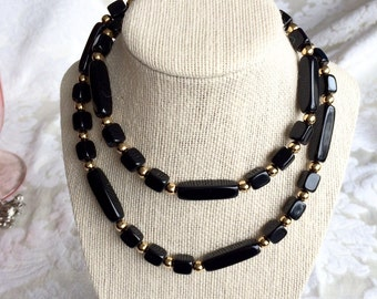 Vintage Signed Trifari Necklace with oblong and rectangle black beads and shiny gold tone spacers.  The necklace measures approx. 30 inches