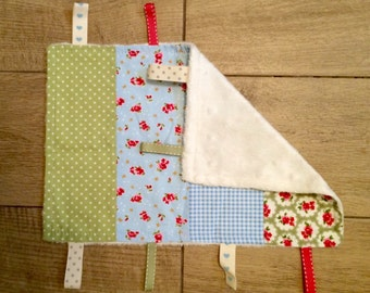 Baby sensory taggie blanket. Blue and green cotton fabrics and soft, cream, minky fabric on revese. Coordinating ribbons.