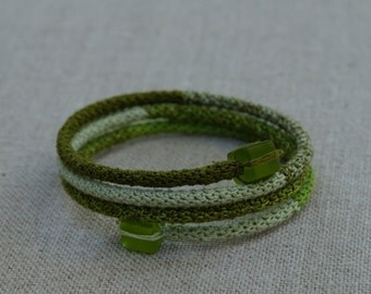 Wrap bracelet in metalthread covered with finecrochet cotton finished with glassbeads,green color combination