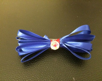 Blue and red loopy bow on a french barrette with a jewel embellishment.