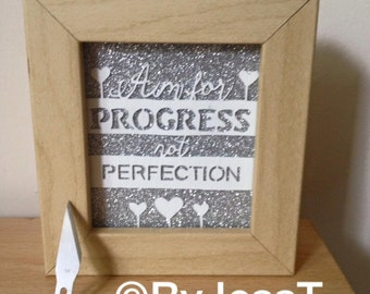 """Miniature paper cut with the quote """"Aim for progress not perfection""""."""