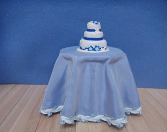 A beautiful 3 tier blue and white wedding or occasion cake, for your dolls house.