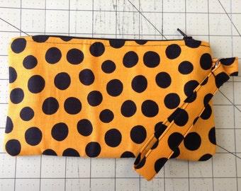 Orange and black polka dot wristlet