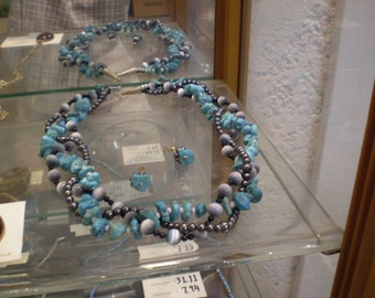 Braided bead necklace of stabilized turquoise and other beads having black and silvery look.
