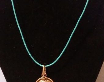 "Bronze ""G"" pendant on a blue hemp necklace"
